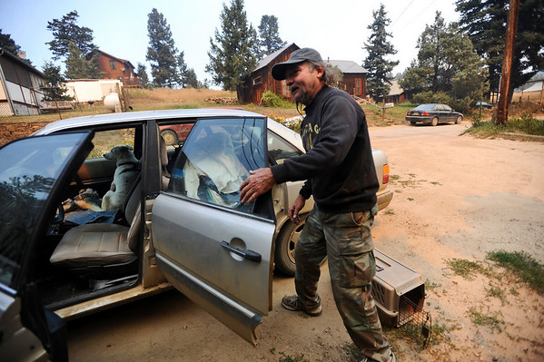 FOURMILE<br /> Tom Colby, who has lived in Gold Hill for 21 years, races to evacuate himself and his dog during the Fourmile Canyon fire on Monday. He was forced to leave his cat, which refused to be caught.<br /> Photo by Marty Caivano/Camera/Sept.6, 2010
