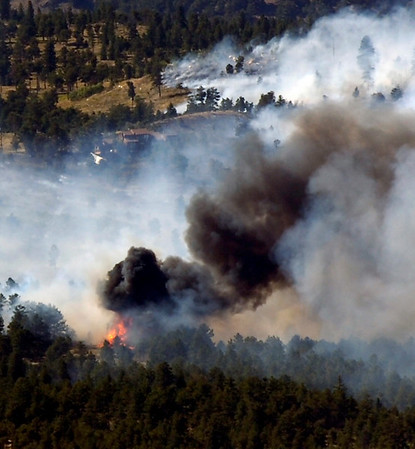 The wildland fire flares up with homes visible in the background as seen from Flagstaff Mountain on Monday afternoon. Photo by Paul Aiken