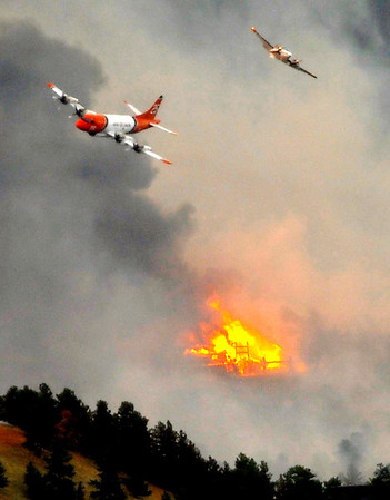 A spotter plane and large slurry bomber past over a burning home in the Fourmile Canyon fire in Boulder, Colorado September 6, 2010.  CAMERA/Mark Leffingwell