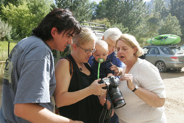 Family members Christine Fisher, right to left, Gene, Jessica, and Chris gather around to view the photos that Chris took while he was up Sunshine Canyon attempting to get to his family's  home Monday afternoon at the Centennial Trailhead in Boulder.  <br /> <br /> <br /> Photo by Patrick Kelley / For The Camera