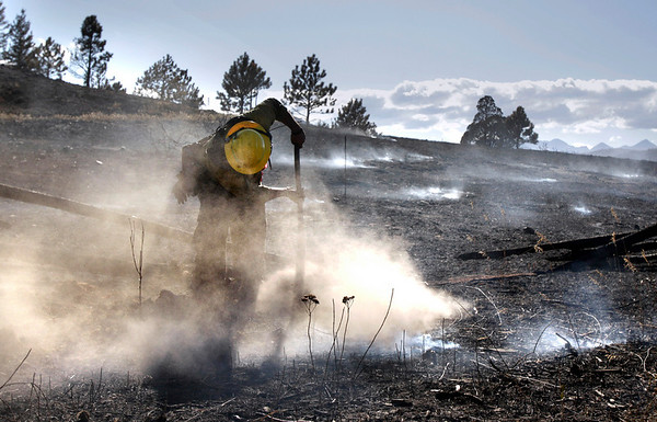Dust rises as firefighter David Yowell mops up hot spots in Sunshine Canyon, west of Boulder, Colo., Friday, Sept. 10, 2010. About 2,000 people were cleared to return, but another 1,000 or so were still kept away because of how close their homes are to the 10-square-mile fire that's still burning. (AP Photo/Jae C. Hong, Pool)