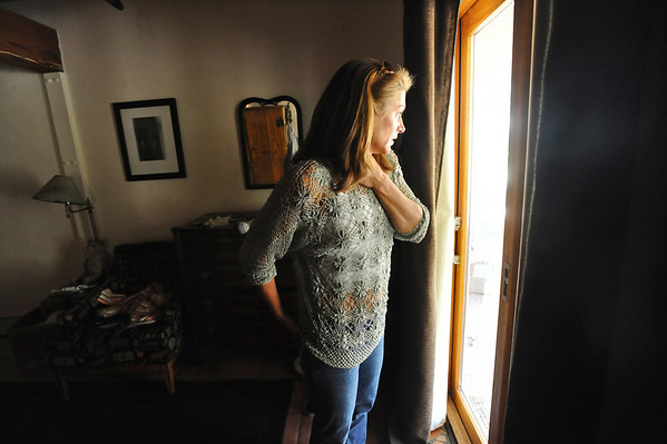 OLDESTAGE01.JPG OLDESTAGE<br /> Leslie Bentson looks out the window of her house on Olde Stage Road after returning home on Friday. The evacuation from the Fourmile Fire has been her third fire evacuation in the almost seven years she has lived there.<br /> Photo by Marty Caivano/Camera/Sept. 10, 2010