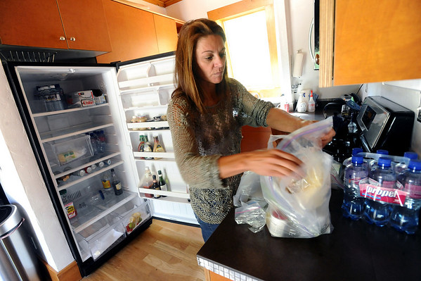 OLDESTAGE03.JPG OLDESTAGE<br /> Leslie Bentson organizes perishable food at her house on Olde Stage Road after returning to it on Friday. Her house had no power or water, so she was doubtful she'd spend the night there. The evacuation from the Fourmile Fire has been her third fire evacuation in the almost seven years she has lived there.<br /> Photo by Marty Caivano/Camera/Sept. 10, 2010