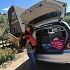 OLDESTAGE02.JPG OLDESTAGE<br /> Leslie Bentson glances up the road while unloading evacuation belongings from her car outside her home on Olde Stage Road on Friday. Her house had no power or water, so she was doubtful she'd spend the night there. The evacuation from the Fourmile Fire has been her third fire evacuation in the almost seven years she has lived there.<br /> Photo by Marty Caivano/Camera/Sept. 10, 2010