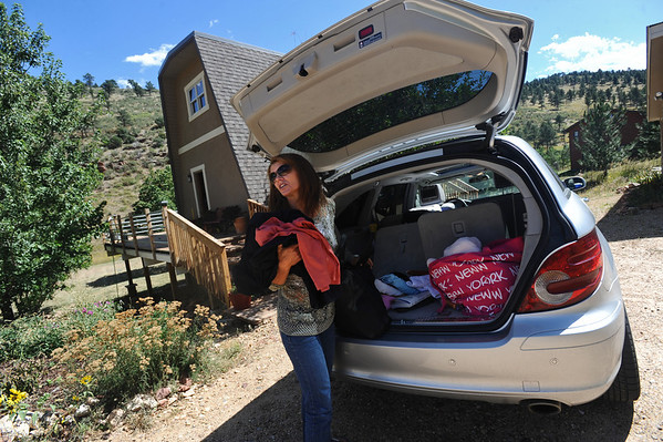 OLDESTAGE<br /> Leslie Bentson glances up the road while unloading evacuation belongings from her car outside her home on Olde Stage Road on Friday. Her house had no power or water, so she was doubtful she'd spend the night there. The evacuation from the Fourmile Fire has been her third fire evacuation in the almost seven years she has lived there.<br /> Photo by Marty Caivano/Camera/Sept. 10, 2010