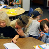 Susanne Porter, of Ward, at right, watches as Gold Hill Elementary student Amitan Bar-Evan, at right and other evacuated students, open their new backpacks full of school supplies on Friday, Sept. 10, at Foothill Elementary School in Boulder. The students that attend Gold Hill Elementary School will be attending at Foothill Elementary until their school is reopened after the Fourmile fire is contained. The family at left asked not to be identified.<br /> Jeremy Papasso/ Camera