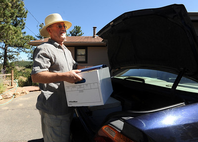 Sheldon Romer moves some of his important papers back into his home on Deer Trail Road on Saturday. Residents in the Boulder Heights area of the Fourmile Fire move back, check on their houses on September 11, 2010. For  videos  and photos relating to the fire,  go to www.dailycamera.com. Cliff Grassmick / September 11, 2010
