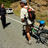 Lee Keiser of Boulder chats with Boulder County Sheriff's Deputy K. Javes at the intersection of Poorman Road and Sunshine Canyon Saturday afternoon. Keiser was turned around at the roadblock. Keiser said he often bikes in the area and was riding up to see the situation for himself.<br /> Photo by Paul Aiken / The Camera