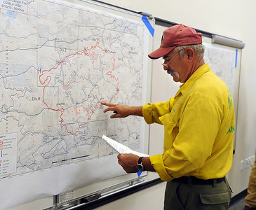 Tom Smith, Operations Chief, checks the information on the latest map on Saturday. Fire fighting staff was busy at the Fourmile Mile Fire Incident center on Saturday. For  videos  and photos relating to the fire,  go to www.dailycamera.com. Cliff Grassmick / September 11, 2010
