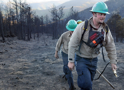 Platte Canyon firefighter Mike Reese, front, walks towards the fire truck with two other firefighters after containing some smoldering wood on Saturday, Sept. 11, just west of Gold Hill. Jeremy Papasso/ Camera