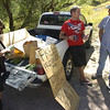 "Terran Wieder, 12, looks over the produce as Jody Proctor, center chats with Drigan Wieder in Sunshine Canyon on Saturday afternoon. Proctor decided after the evacuation to offer his garden bounty to locals in need. The Wieders stopped to thank him for his charity but declined to take anything. ""People need it more than we do,"" Drigan Wieder said. Neither family lost their homes.<br /> Photo by Paul Aiken / The Camera"