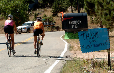 Cyclists pass a thank you sign on  their way up Deer Trail Road in Boulder Heights on Saturday. Residents in the Boulder Heights area of the Fourmile Fire move back, check on their houses on September 11, 2010. For  videos  and photos relating to the fire,  go to www.dailycamera.com. Cliff Grassmick / September 11, 2010