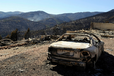 A burned car sits in the driveway of a destroyed home on Sunshine Canyon Drive while wildfire smoke rises in the distance on Saturday, Sept. 11. The Fourmile Canyon fire destroyed many houses and huge portions of land. For video go to www.dailycamera.com Jeremy Papasso/ Camera