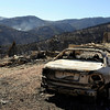 "A burned car sits in the driveway of a destroyed home on Sunshine Canyon Drive while wildfire smoke rises in the distance on Saturday, Sept. 11. The Fourmile Canyon fire destroyed many houses and huge portions of land.<br /> For video go to  <a href=""http://www.dailycamera.com"">http://www.dailycamera.com</a><br /> Jeremy Papasso/ Camera"