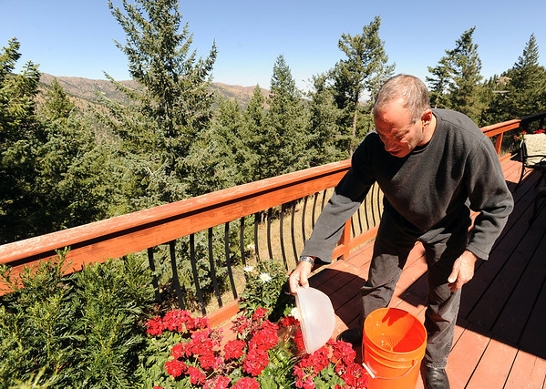"""Sandy Fisher water the plants at his home on Tall Pine Road on Saturday.<br /> Residents in the Boulder Heights area of the Fourmile Fire move back, check on their houses on September 11, 2010.<br /> For  videos  and photos relating to the fire,  go to  <a href=""""http://www.dailycamera.com"""">http://www.dailycamera.com</a>.<br /> Cliff Grassmick / September 11, 2010"""