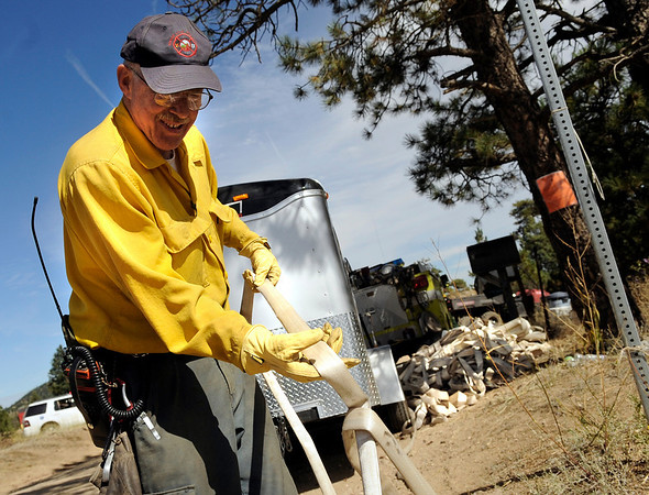 Firefighter Bob Mann, of the Sugarloaf Volunteer Fire Department, winds up a fire-hose after it was no longer needed on Sunday, Sept. 12, on Mountain Pines Road in Boulder County. Several houses in the area were destroyed by the Fourmile Canyon Fire, however some homes were miraculously unaffected.<br /> Jeremy Papasso/ Camera