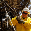 Xcel Energy employee Craig Bibee cuts some downed power lines on Sunday, Sept. 12, on Mountain Pines Road in Boulder County. Several houses in the area were destroyed by the Fourmile Canyon Fire, however some homes were miraculously unaffected.<br /> Jeremy Papasso/ Camera