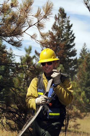 "Dal Leck, of West Routt Fire Department carries a hose back to the fire truck on Sunday, Sept. 12, near Mountain Pines Road in Boulder County.<br /> For video and photo gallery go to  <a href=""http://www.dailycamera.com"">http://www.dailycamera.com</a><br /> Jeremy Papasso/ Camera"