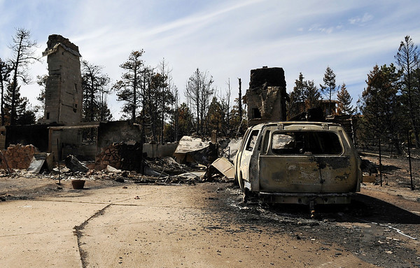 A burned vehicle sits in the driveway of a destroyed home on Sunday, Sept. 12, on Mountain Pines Road in Boulder County. Several houses in the area were destroyed by the Fourmile Canyon Fire, however some homes were miraculously unaffected.<br /> Jeremy Papasso/ Camera