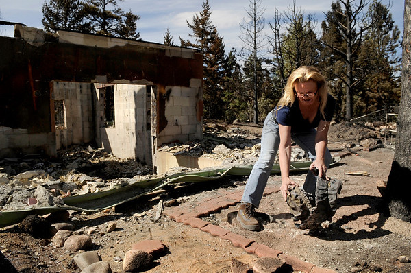 "Elizabeth Wallace picks up a piece of bronze artwork that was burned along with her home on Sunday, Sept. 12, at the Wallace residence on Mountain King Road in Boulder County.<br /> For video and photo gallery go to  <a href=""http://www.dailycamera.com"">http://www.dailycamera.com</a><br /> Jeremy Papasso/ Camera"