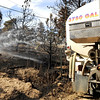A water tanker sprays water on a smoldering stump on Sunday, Sept. 12, on Mountain Pines Road in Boulder County. Several houses in the area were destroyed by the Fourmile Canyon Fire, however some homes were miraculously unaffected.<br /> Jeremy Papasso/ Camera