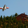 A slurry bomber passes near a home while lining up for a drop on the north side of the Fourmile Canyon fire in Boulder, Colorado September 7, 2010.  CAMERA/Mark Leffingwell