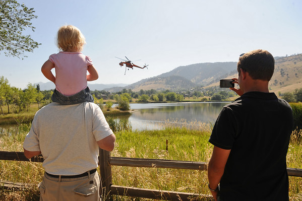 4MILETUES<br /> Katie McDaniel, 1, sits on the shoulders of Mike McDaniel, left, while Tyler Bowron uses his phone to photograph a helicopter that was drawing water from Wonderland Lake to fight the Fourmile Canyon Fire on Tuesday. <br /> Photo by Marty Caivano/Camera/Sept.7, 2010