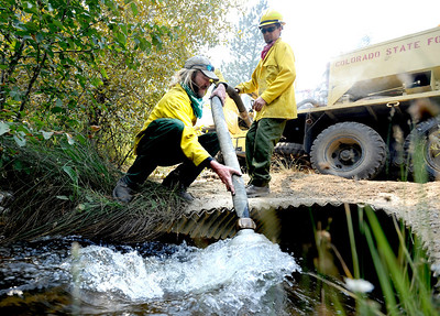 Tim O'Connor (left) and Scott Porter (right), both with Indian Peaks Fire, get water from a creek to fill their 1000 gallon fire truck while fighting the Fourmile Canyon fire in Boulder, Colorado September 7, 2010.  CAMERA/Mark Leffingwell