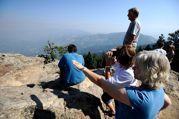 Pat Spence, a resident of the area between Lee Hill and Sugarload, points out to the possible location of the family home to her emergency host Carolyn Geer on Flagstaff Mountain on Tuesday morning. Spence's husband David stands at the right. <br /> Photo by Mark Leffingwell / The Camera