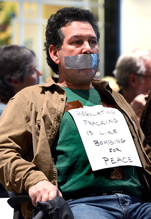 "OIL_AND_GAS_8613.jpg Paul Bassis, of Louisville, protests silently while wearing a ""regulating fracking is like bombing for peace"" sign, Thursday, Dec. 13, 2012, at the Boulder County Courthouse.<br /> (Jeremy Papasso/Daily Camera)"