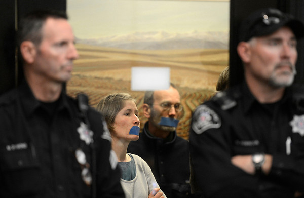 Oil_AND_GAS_8603.jpg Marion Frebourg, of Longmont, center, left, is seen silently protesting through the meeting room doors between two Boulder County Sheriffs Deputies, Thursday, Dec. 13, 2012, at the Boulder County Courthouse.<br /> (Jeremy Papasso/Times-Call)