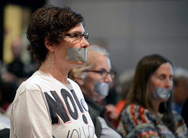 """Fracking002.JPG Anti-fracking supporter Diana Devine listens with duck tape over her mouth during meeting on fracking on Thursday, Dec. 13, at the County Courthouse on Pearl Street in Boulder. For more photos and video of the tracking protest go to  <a href=""""http://www.dailycamera.com"""">http://www.dailycamera.com</a><br /> Jeremy Papasso/ Camera"""