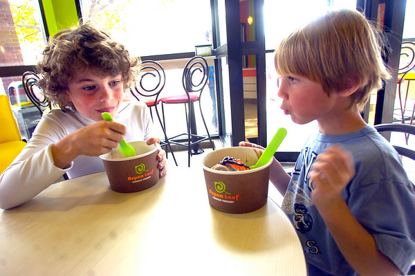 """Trevor Fox, 7, right, takes a break from eating because of his """"brain freeze: while Ian Capdevielle, 9 at left tucks into his yogurt at Aspen Leaf Yogurt in the Table Mesa Shopping Center in Boulder on Tuesday.<br /> Photo by Paul Aiken / The Camera / May 3, 2011"""