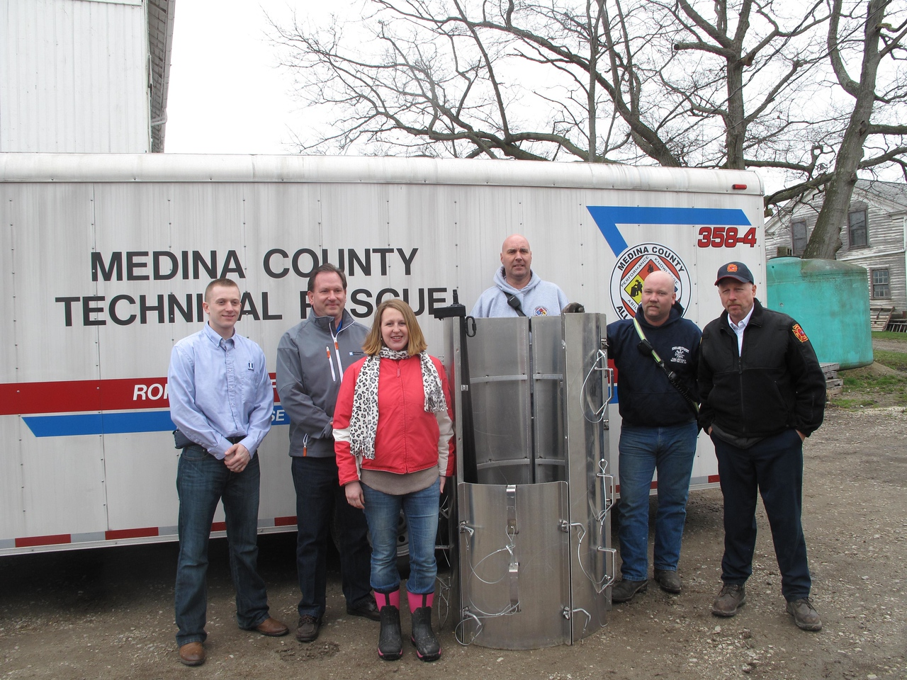 ELIZABETH DOBBINS / GAZETTE Trent Insurance Group agent Travis Mills, Trent Insurance Group agent Greg Trent, Medina County Farm Bureau President Sarah Poling, Brunwsik firefighter and technical rescue team liaison Wally Sobczyk, Chatham Firefighter and member of the Medina County All Hazards Team Jon Ulferts and Chatham Fire Chief Bill Disbrow stand near one of the new rescue tubes.