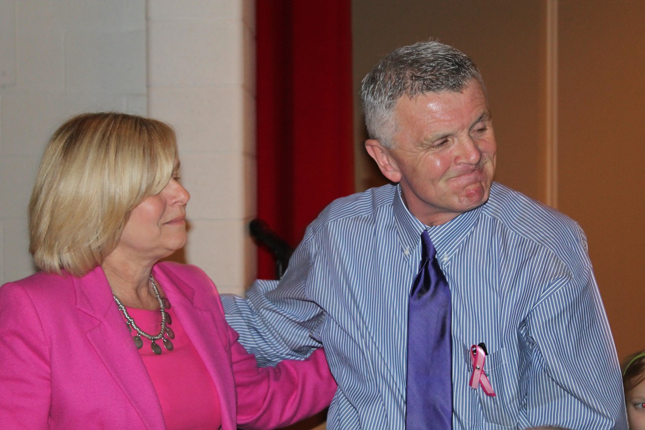 LAWRENCE PANTAGES / GAZETTE Isham Elementary School 4th grade teacher Diane Lukens, left, shares a moment Thursday with Denny Farver during a ceremony at which the library was renamed for Farver's late wife, Heidi Currens Farver. Mrs. Farver died in February after a 2-year fight with breast cancer.