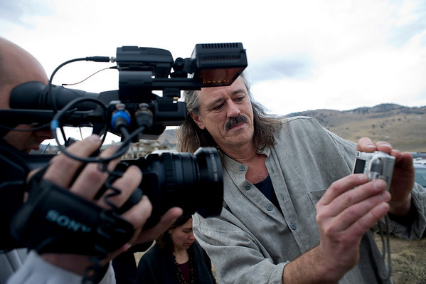 Shano Kelley, of Boulder, shows TV crews a picture of an airplane and glider crash near where U.S. 36 meets with Broadway just outside of Boulder, Saturday, Feb. 6, 2010. <br /> KASIA BROUSSALIAN
