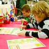 Six-year-olds Hunter Morgan and Micah Morris color flag pictures at the Hussey-Mayfield Memorial Public Library Saturday, Dec. 7, during the library's Holiday Stroll. Hunter is the son of Kim Morgan, and Micah is the son of Kyle and Joy Morris.