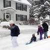 Rev. Michael Tuck, wife Annie Haftl and children Porter, (seated) and Holly enjoy new fallen snow in downtown Lenox on Thursday. Richard Lindsay — The Berkshire Eagle