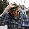 ELODIE REED - FOR THE BENNINGTON BANNER Don Bailey holds onto his hat while feeding cracked corn to the ducks along Park Street in Bennington on Saturday.