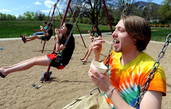 """Jed Storie, right, a University of Wyoming students, swings with his Boulder friends while eating ice cream.<br /> Several people took advantage of the warm Saturday by playing at Scott Carpenter Park.<br /> For more photos and a video at Scott Carpenter Park, go to  <a href=""""http://www.dailycamera.com"""">http://www.dailycamera.com</a>.<br /> Cliff Grassmick/ May 7, 2011"""