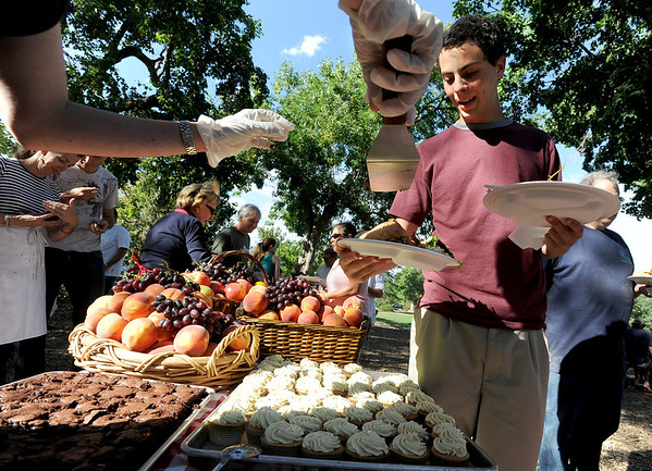"Daniel Sherman, right, gets serves food during the relief picnic. His home is fine, but without electricity.<br /> Evacuees from the Four Mile Fire,  firefighters, volunteers, and others were given an all family fire relief picnic dinner at Chautauqua on Thursday, provided by Colorado Chautauqua and Boulder's top chefs.<br /> For a video and more photos from the picnic,  go to  <a href=""http://www.dailycamera.com"">http://www.dailycamera.com</a>.<br /> Cliff Grassmick / September 16, 2010"