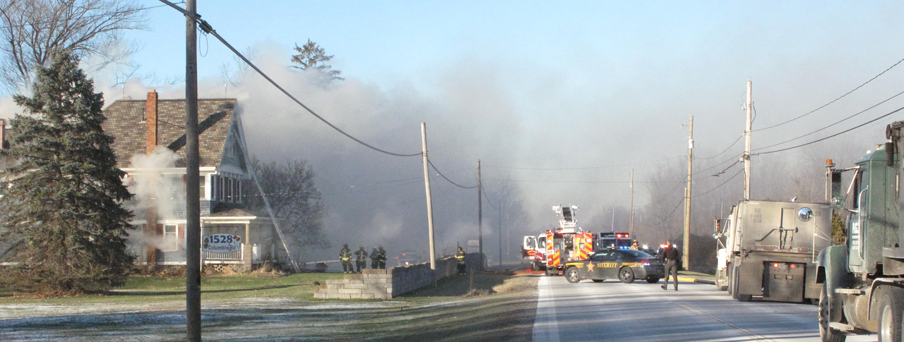 KATIE ANDERSON / GAZETTE Firefighters battle a house fire Tuesday afternoon at 1496 Columbia Road in Liverpool Township. The home is owned by Dave and Lisa Jilbert, who live there and own the Jilbert Winery next door. No one was injured in the fire.
