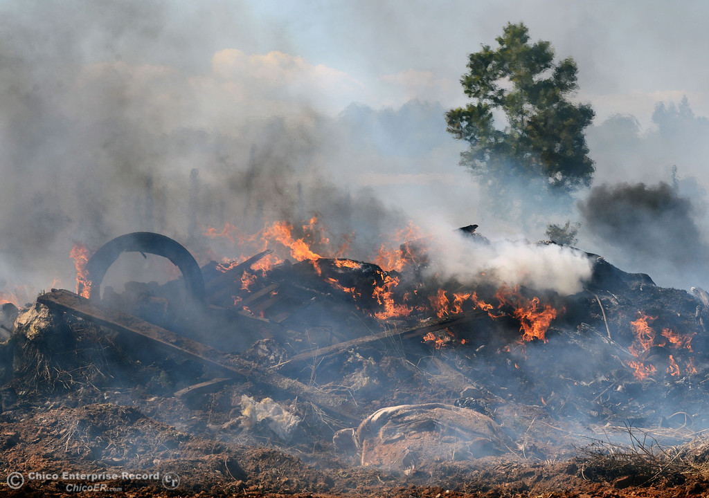 . A debris pile burns as Oroville Fire, El Medio Fire, and Cal Fire - Butte County battle a fire along Power House Hill Rd and Dad Lane that burned several structures and debris piles Thursday, September 26, 2013, in Oroville, Calif.  (Jason Halley/Chico Enterprise-Record)