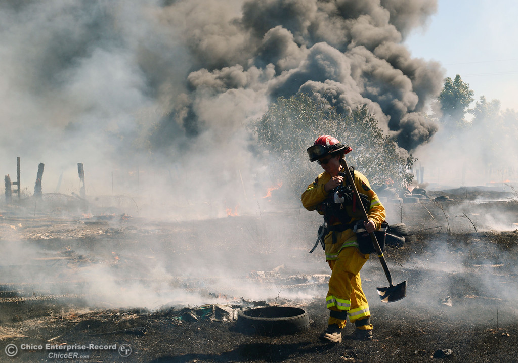 . Cal Fire - Butte County Capt. Lydia Soileau with Oroville Fire and El Medio Fire battle a fire along Power House Hill Rd and Dad Lane that burned several structures and debris piles Thursday, September 26, 2013, in Oroville, Calif.  (Jason Halley/Chico Enterprise-Record)