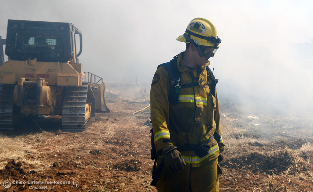 . El Medio firefighter Chris Lewis (right) with Oroville Fire, and Cal Fire - Butte County battle a fire along Power House Hill Rd and Dad Lane that burned several structures and debris piles Thursday, September 26, 2013, in Oroville, Calif.  (Jason Halley/Chico Enterprise-Record)