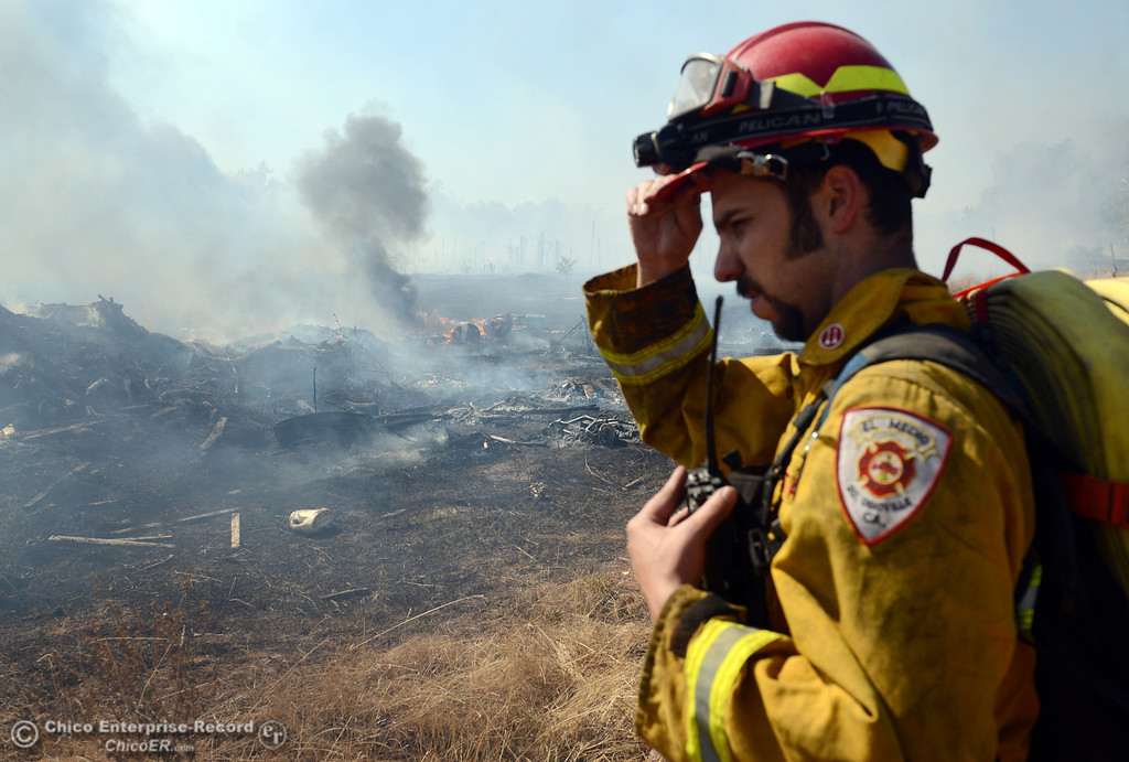 . El Medio Fire Capt. Donald Robinson with Oroville Fire, and Cal Fire - Butte County battle a fire along Power House Hill Rd and Dad Lane that burned several structures and debris piles Thursday, September 26, 2013, in Oroville, Calif.  (Jason Halley/Chico Enterprise-Record)