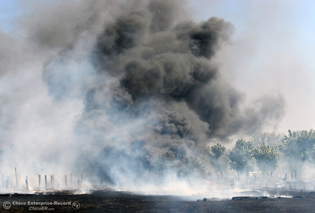 . Dark smoke from a tire pile burns as Oroville Fire, El Medio Fire, and Cal Fire - Butte County battle a fire along Power House Hill Rd and Dad Lane that burned several structures and debris piles Thursday, September 26, 2013, in Oroville, Calif.  (Jason Halley/Chico Enterprise-Record)