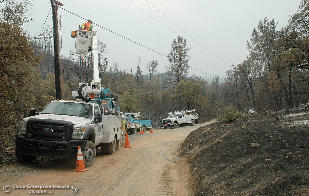 . PG&E crews work on a burned tap line and replace poles  Monday on Chinese Wall Road, off Swedes Flat Road.  Swedes Fire Monday, Aug. 19, 2013.  (Barbara Arrigoni/Staff Photo)