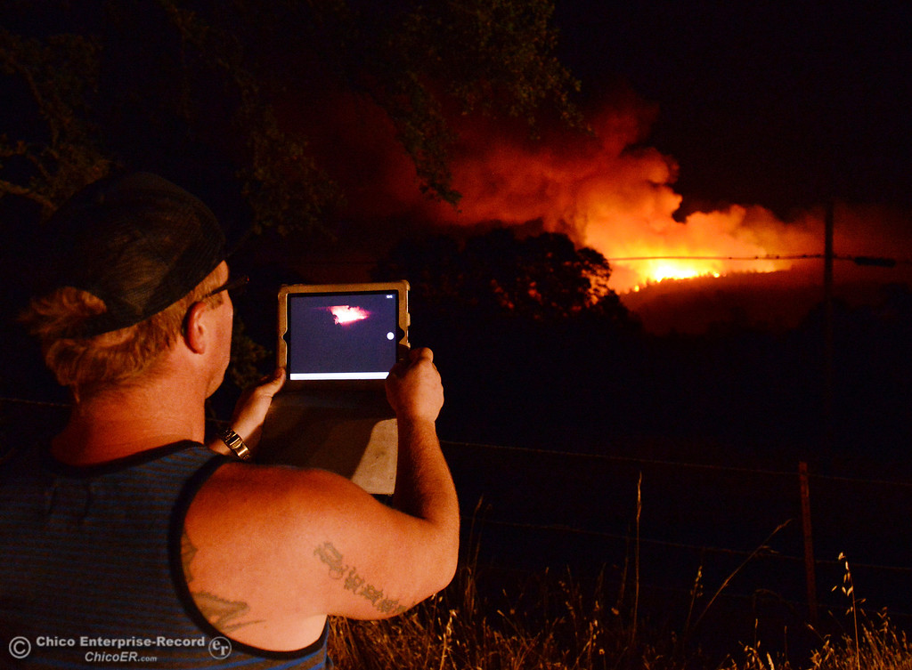 . Jordan Perkins take a photo on his iPad of the Swedes Fire that burns into the night as seen from Oro Bangor Highway, in the vicinity of Chinese Wall Road and Swedes Flat Road Friday, August 16, 2013 in Oroville, Calif. Over 200 acres were burned with at least one structure lost. (Jason Halley/Chico Enterprise-Record)