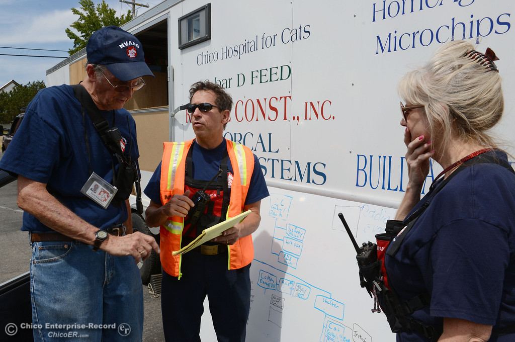. North Valley Animal Disaster Group David Bequette, John Maretti, and Sandy Doolittle (left to right) coordinate a horse rescue at a home under mandatory evacuation areas around the Swedes Fire southeast of Oroville that were expanded just after noon Saturday, August 17, 2013 in Oroville, Calif.  (Jason Halley/Chico Enterprise-Record)
